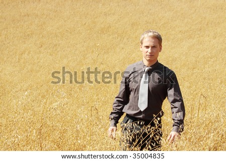Young modern farmer in suit standing in field of oats