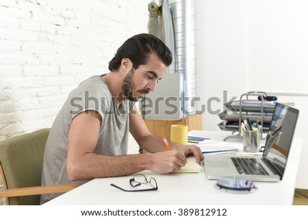 young modern hipster style student or businessman working with laptop computer at home office writing with pen in pad in creative freelance business success concept