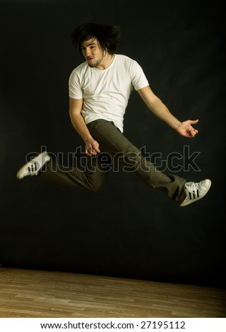 Young modern man dancing over a black background - stock photo