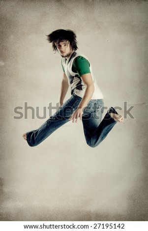 Young modern man jumping over grunge background - stock photo