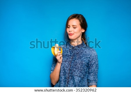 young modern woman eating a banana in hands on blue background - stock photo