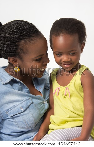 Young Mom is Talking to her Toddler Daughter - stock photo