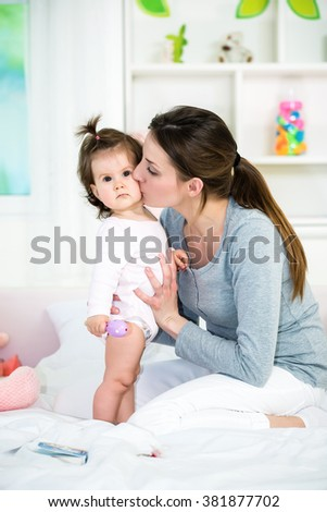 Young mom kissing her baby girl on the bed.Baby standing and looking at camera.Shallow doff - stock photo