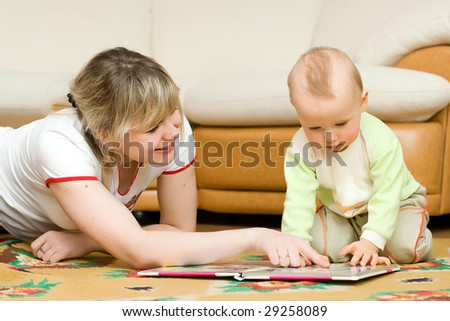 Young mom reading her little son book on a floor