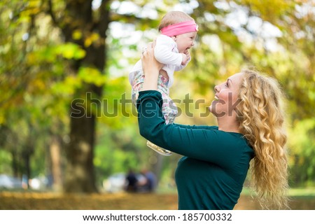 Young mom with baby in park, happy together - stock photo