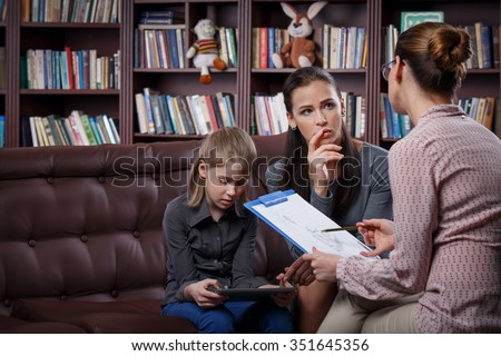 Young mom with her daughter at psychologist consultation  - stock photo