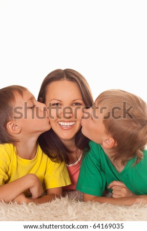 young mom with her two children on a light background