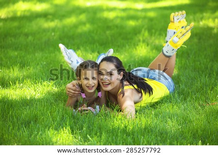 Young mom with her 6 years old child rollerskating in park - stock photo