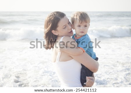 Young mom with son playing at the beach - stock photo