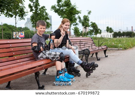 Young mom with ten years old son resting on the bench in urban park while rollerblading