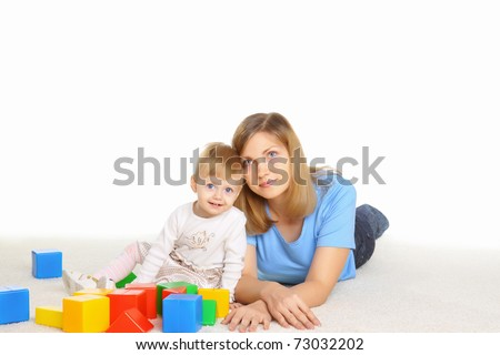 Young mommy playing with her daughter on the floor - stock photo