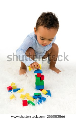 Young 18 month old toddler boy playing with wooden colorful blocks - stock photo