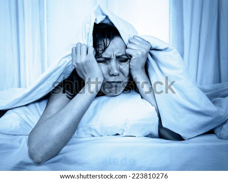 young moody woman in bed suffering stress with her insomnia problem and sleeping disorder or hangover covering with blanket and bedclothes on studio blue lighting - stock photo