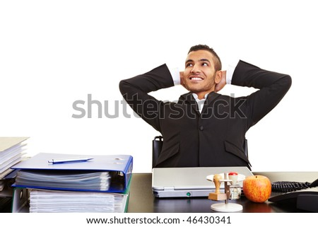 Young moroccan manager leaning back at his desk - stock photo