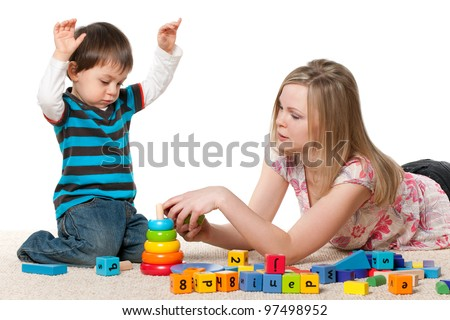 Young mother and a little son are playing on the carpet with blocks; isolated on the white background - stock photo