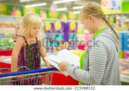 Young mother and adorable daughter in shopping cart select kids books in supermarket