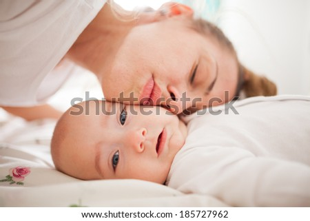 Young mother and baby boy cheek to cheek