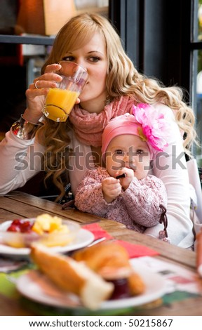 Young mother and baby daughter having breakfast together in a Parisian cafe - stock photo
