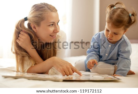 young mother and baby girl reading book together - stock photo
