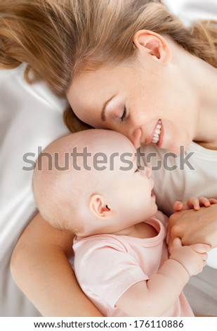 young mother and baby lying in bed