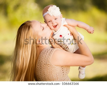 young mother and baby outdoor on a warm summer day - stock photo