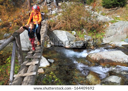 Young mother and child crossing a stream of water on the mountain - stock photo