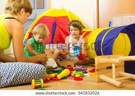 Young mother and children playing with  toys in home - stock photo