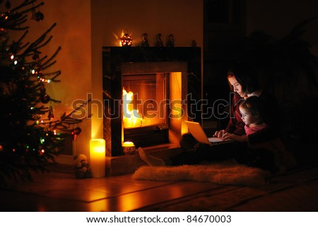 Young mother and daughter by a fireplace on Christmas - stock photo