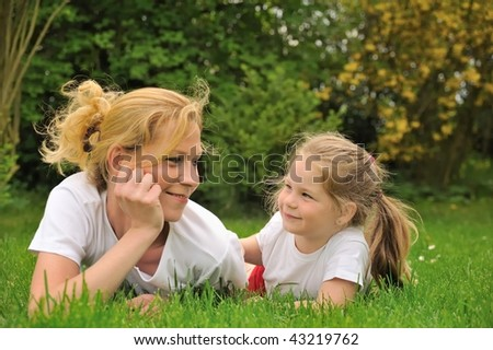 Young mother and daughter laying on the grass