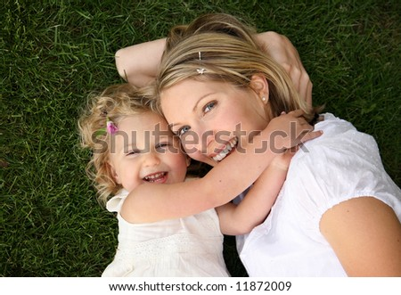young mother and daughter laying together on grass - stock photo