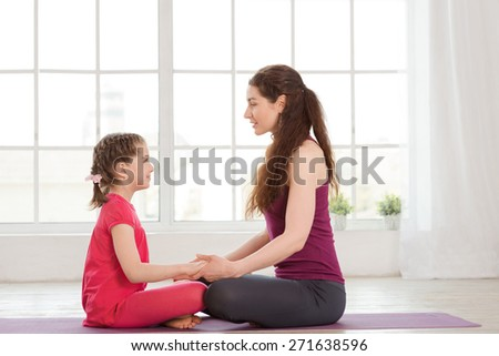 Young mother and daughter looking at each other when doing yoga exercise in fitness studio with big windows on background - stock photo
