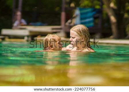 Young mother and daughter swimming in crystal clear laguna on tropical island - stock photo