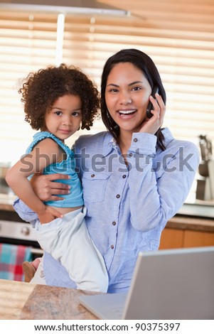 Young mother and daughter using cellphone in the kitchen together