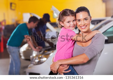 young mother and daughter waiting in garage while father talking to mechanic - stock photo