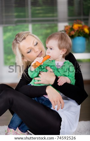 young mother and daughter with carrot, a studio portrait