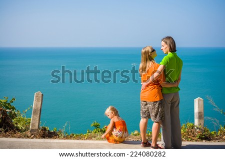 Young mother and father embraces and daughter stay on mountain road along tropical island beach and look at ocean - stock photo