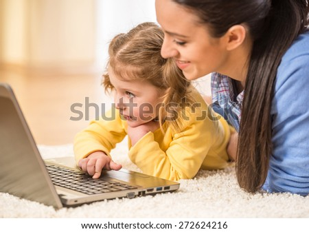 Young mother and her adorable daughter are using laptop while lying on the floor. - stock photo