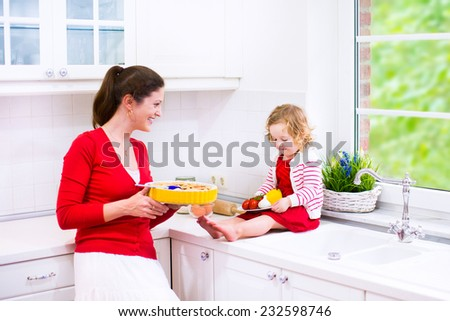 Young mother and her adorable daughter, cute funny toddler girl in a red dress, baking a pie together preparing healthy lunch in a white sunny kitchen with window - stock photo