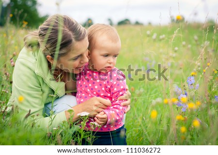 Young mother and her baby girl playing while outdoors on a walk
