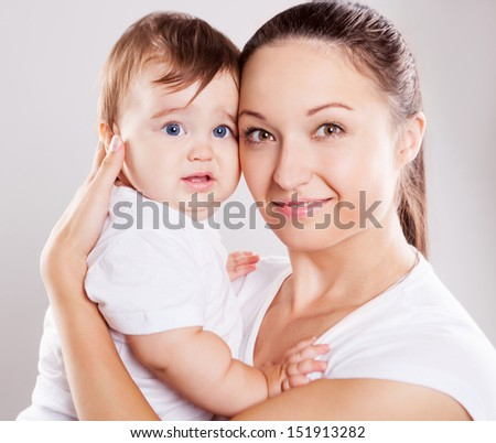 young mother and her baby in the studio, isolated on white background - stock photo