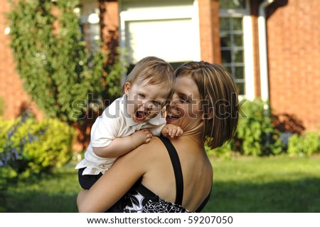 Young mother and her baby son play in the backyard. - stock photo