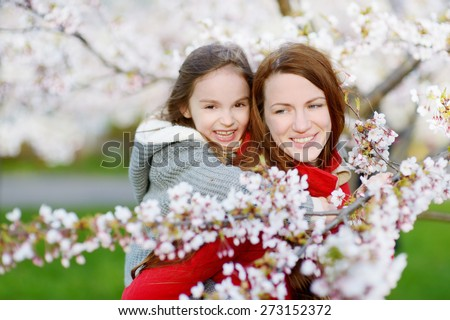 Young mother and her child in blooming cherry garden on beautiful spring day - stock photo
