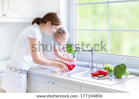 Young mother and her cute curly toddler daughter washing vegetables together in a kitchen sink getting ready to make salad for lunch in a sunny white kitchen with a big garden view window - stock photo