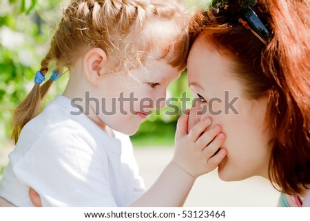 Young mother and her cute little daughter touching each other foreheads. - stock photo