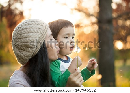 Young mother and her cute son blowing dandelion flowers together.
