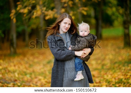 Young mother and her cute toddler daughter at fall