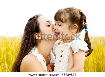 young mother and her daughter at the wheat field on a sunny day (focus on the mother) - stock photo