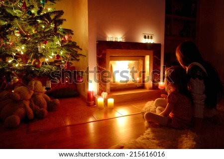 Young mother and her daughter by a fireplace on Christmas - stock photo