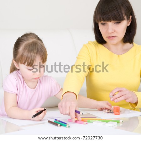 young mother and her daughter having fun in kindergarden