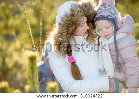 Young mother and her daughter having fun on winter day